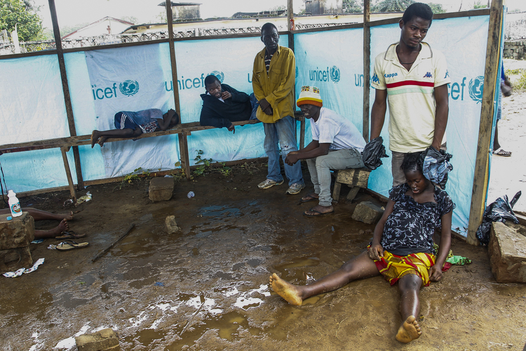 ATTENTION MUST BE PAID. Liberians wait outside the John F. Kennedy Ebola treatment center in Monrovia, Liberia, Sept. 18.