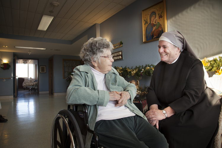 Sister Michael Mugan visits Jan. 13 with resident Pat Austin in the hallway of the St. Louis Residence of the Little Sisters of the Poor, which serves about 100 people. (CNS photo/Lisa Johnston, St. Louis Review)