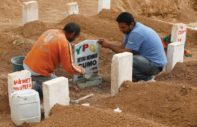 FINAL REST. Men place a headstone at the grave of Seydo Mehmud Cumo, 44, at a cemetery in Suruc, Turkey, Oct. 11. Cumo was a Syrian Kurdish fighter killed in clashes with Islamic State militants in Kobani, Syria.