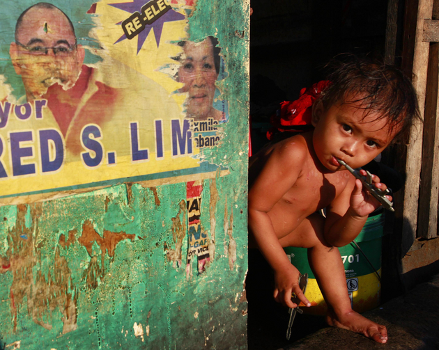 A boy brushes his teeth along a road in a slum outside Manila, Philippines (CNS photo/Nicky Loh, Reuters)