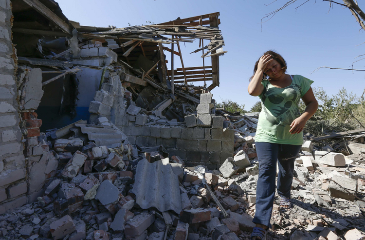 A woman walks at her destroyed house in the village of Kominternovo, Ukraine, near the southern coastal town of Mariupol in September. (CNS photo/Vasily Fedosenko, Reuters)