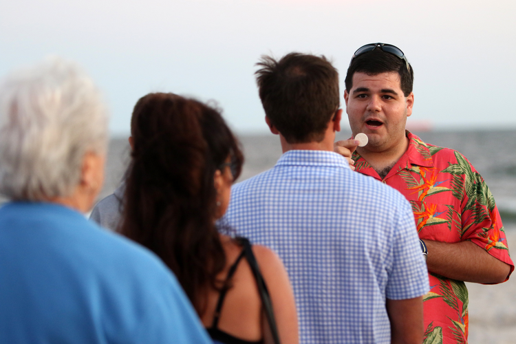 ALL ARE WELCOME. Seminarian Matt Browne distributes Communion during a beach Mass in Long Beach, N.Y., Sept. 6 (CNS photo/Gregory A. Shemitz, Long Island Catholic).
