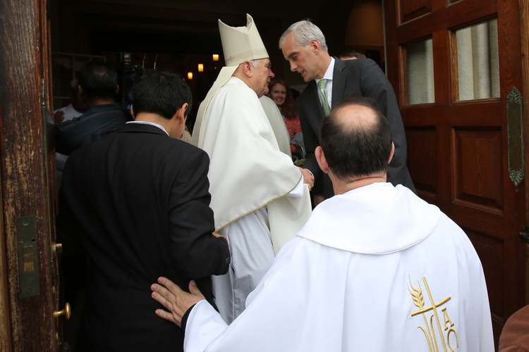 "Miami Archbishop Thomas G. Wenski greets Denis McDonough, White House chief of staff, after celebrating the ""Mission for Migrants"" Mass May 29 at St. Peter's Catholic Church on Capitol Hill in Washington."