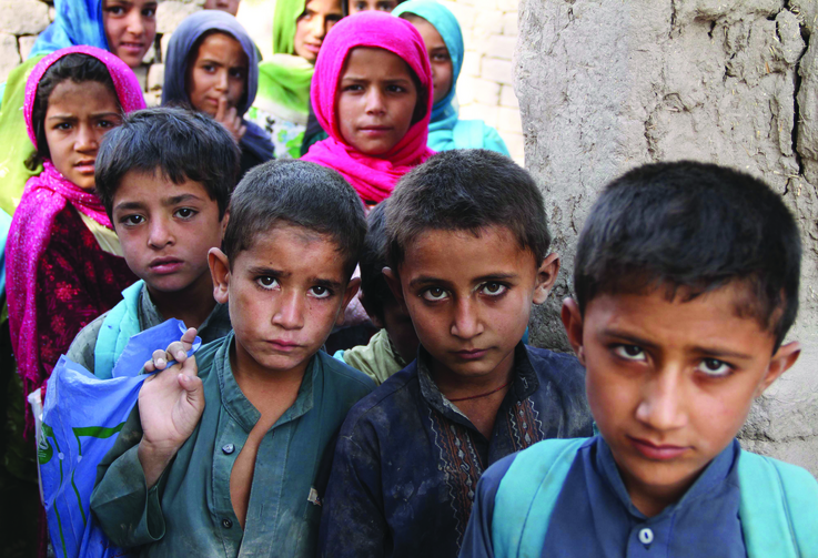 GETTING TO CLASS. Afghan children arrive at a school near a refugee camp near Kabul.