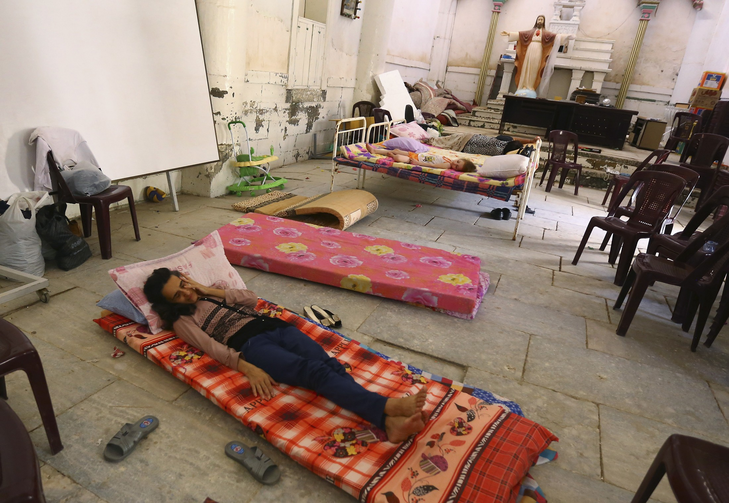 An Iraqi Christian family fleeing the violence in Mosul sleeps inside Sacred Heart of Jesus Chaldean Church in Telkaif, Iraq, Mosul July 20. Pope Francis called for prayers, dialogue, and peace, as the last Iraqi Christians flee Mosul.