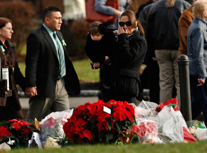 People walk past a memorial site following Jessica Rekos' funeral Mass at St. Rose of Lima Church in Newtown, Conn., Dec. 18. Photo: CNS.