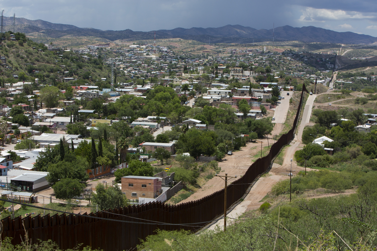 The international border fence snakes along hills in this July 16 view from east of Nogales, Ariz. Nogales in Sonora, Mexico, is more densely populated than that of its U.S. sister city.