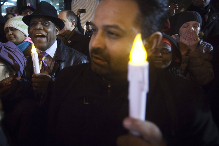 Community members join a prayer vigil on Dec. 22 at the site of the officers' murder in Brooklyn. (CNS photo/Carlo Allegri, Reuters)