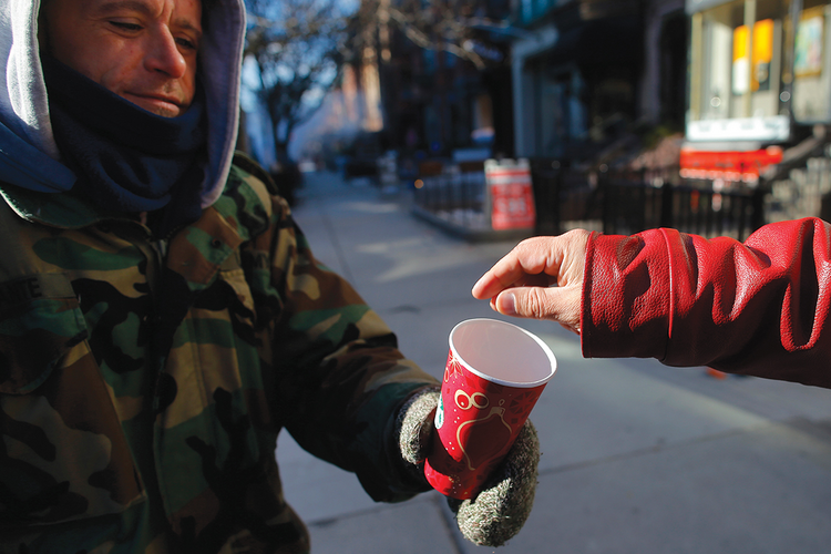 FOR YOUR SERVICE. A passerby gives some money to Chris, a homeless veteran of the United States' wars in Iraq and Afghanistan, on Newbury Street in Boston, Mass.