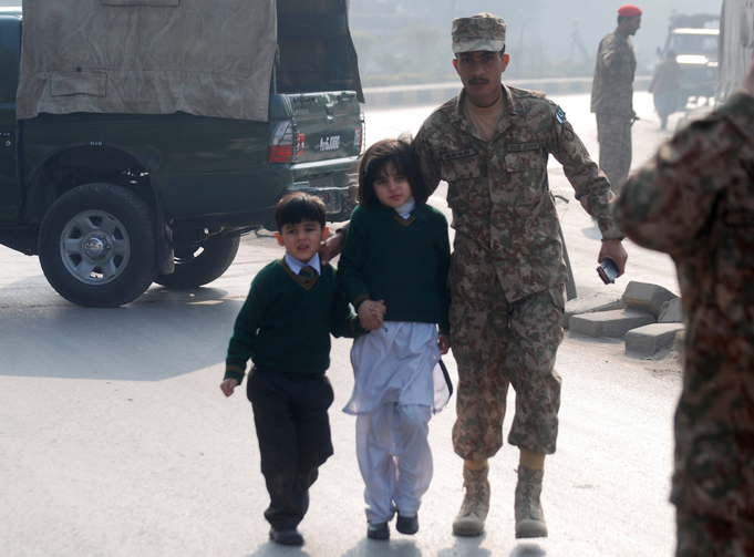 A soldier escorts schoolchildren from the Army Public School attacked Dec. 16 by Taliban gunmen in Peshawar, Pakistan. (CNS photo/Khuram Parvez, Reuters)