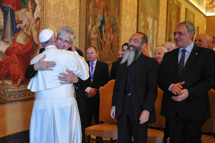Pope embraces Father Guillermo Marco (his former press officer), as Rabbi Daniel Goldman and Islamic leader Omar Abboud look on.