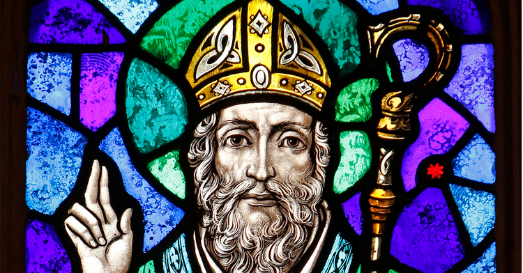 "St. Patrick is depicted in a stained-glass window at St. Aloysius Church in Great Neck, N.Y. Archbishop Eamon Martin of Armagh, Northern Ireland, said that ""as Irish people, we cannot think of St. Patrick without acknowledging the enormous humanitarian and pastoral challenges facing growing numbers of people who find themselves displaced and without status in our world."" (CNS photo/Gregory A. Shemitz)"