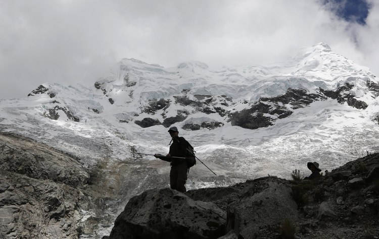 People walk near the Hualcan Glacier in the Ancash region of Peru Nov. 29. Peru is hosting the annual U.N. Climate Change Conference (COP20) in Lima Dec. 1-12. (CNS photo/ Mariana Bazo, Reuters)