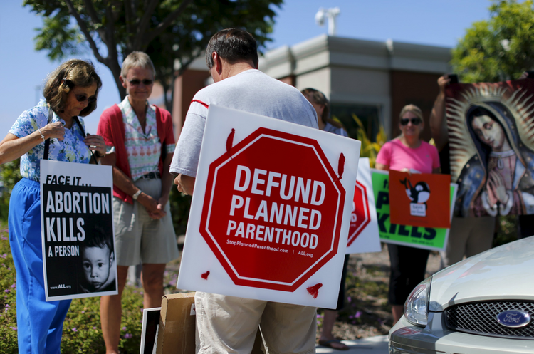 Protesters carry signs and an image of Our Lady of Guadalupe outside a Planned Parenthood clinic in Vista, Calif., Aug. 3 (CNS photo/Mike Blake, Reuters).