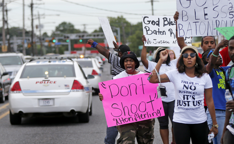 Police cars pass demonstrators on July 6 in Baton Rouge, La. Alton Sterling, a black man, was shot and killed by two white officers on July 5 outside a convenience store (AP Photo/Gerald Herbert).