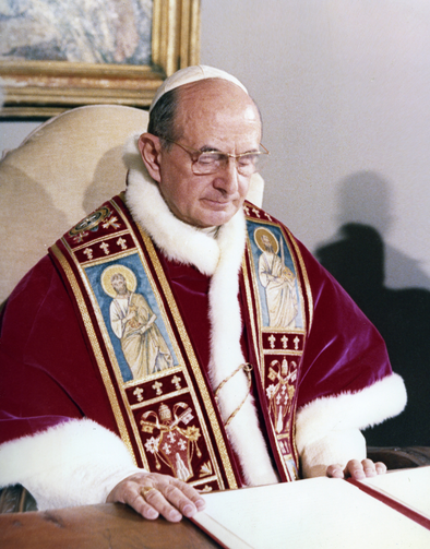 Pope Paul VI featured at his desk in the Vatican.