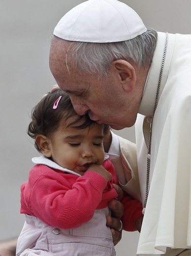 Pope Francis kisses a young girl as he leaves his general audience in St. Peter's Square at the Vatican, Oct. 29 (CNS Photo, Paul Haring).