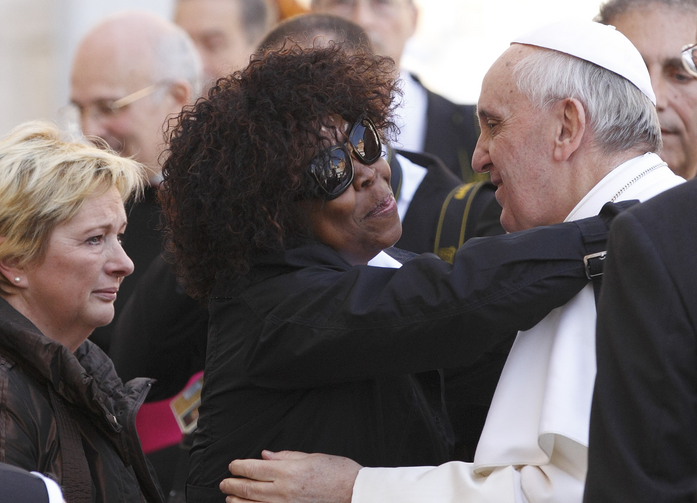 Patience Dodo of Gabon, who is blind, hugs Pope Francis as he leaves his general audience in St. Peter's Square at the Vatican, April 10, 2013.