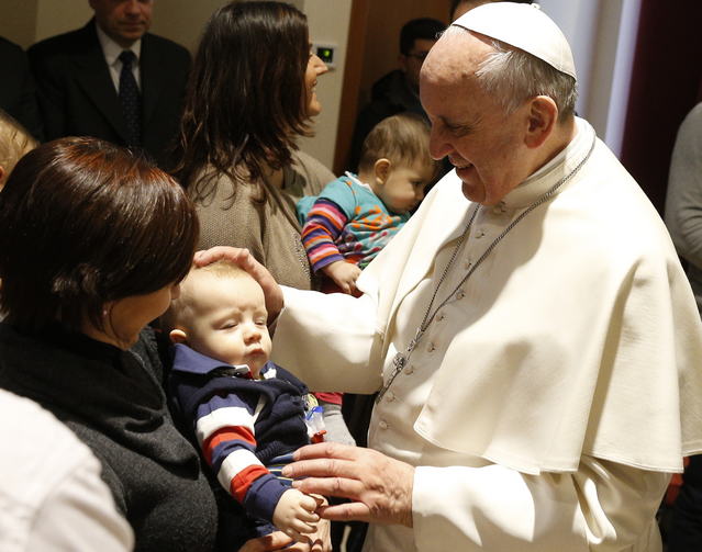 Pope Francis blesses a baby as he visits St. Thomas the Apostle Parish on the outskirts of Rome on Feb. 16