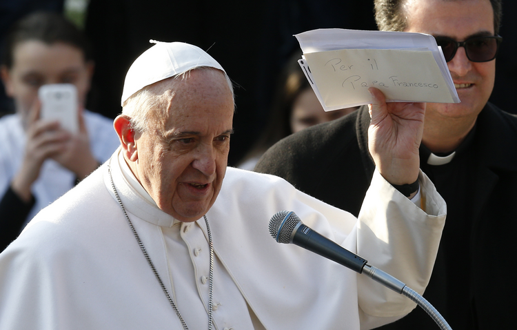 Pope Francis holds up letters he received from young people during a visit to St. Mary Mother of the Redeemer Parish on the outskirts of Rome March 8. (CNS photo/Paul Haring)
