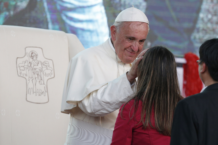 Pope Francis greets a young woman as he leads a meeting with young people in Asuncion, Paraguay, July 12 (CNS photo/Paul Haring).