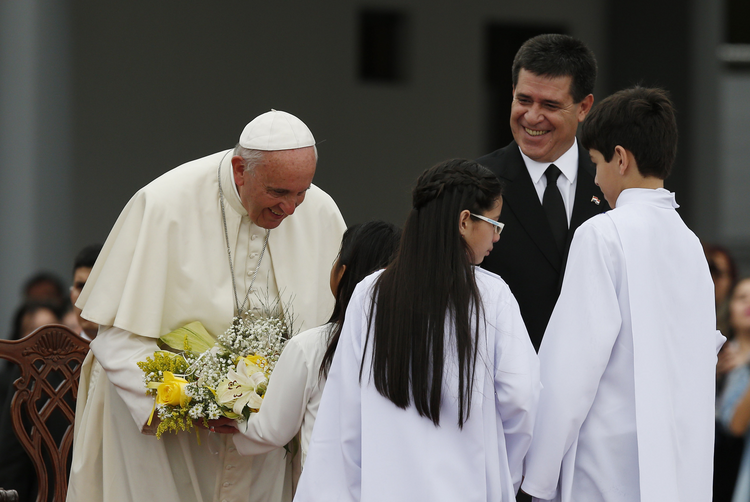Pope Francis receives flowers at Silvio Pettirossi International Airport in Asuncion, Paraguay, July 10 (CNS photo/Paul Haring).