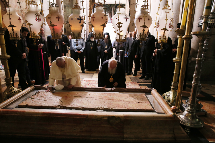Pope Francis and Ecumenical Patriarch Bartholomew of Constantinople venerate the Stone of Unction in Jerusalem's Church of the Holy Sepulcher on May 25.
