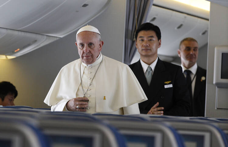 Pope Francis walks down aisle aboard flight from Seoul to Rome, August 18.