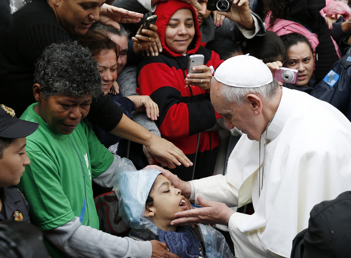 Pope Francis blesses boy during visit to slum complex in Brazil, July 25 (CNS Photo / Paul Haring)
