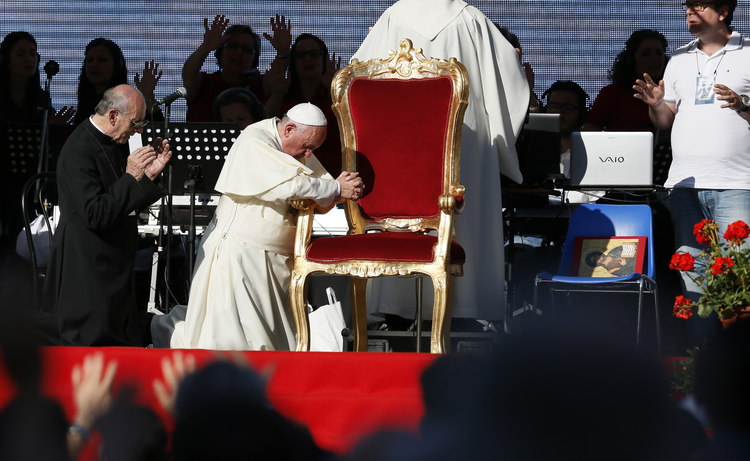 Pope Francis kneels as the crowd prays over him by singing and speaking in tongues during an encounter with more than 50,000 Catholic charismatics at the Olympic Stadium in Rome on June 1.