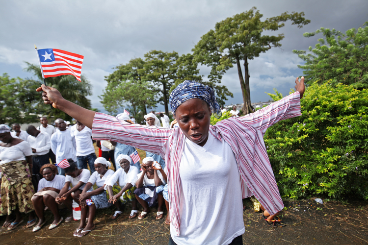 A Liberian woman prays for the end of Ebola outside Monrovia, Liberia, last October.