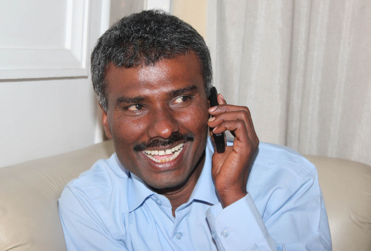 Jesuit Father Alexis Prem Kumar, who was kidnapped in Afghanistan and was held for more than eight months, speaks on a cell phone on his arrival in New Delhi Feb. 22. (CNS photo/Anto Akkara)