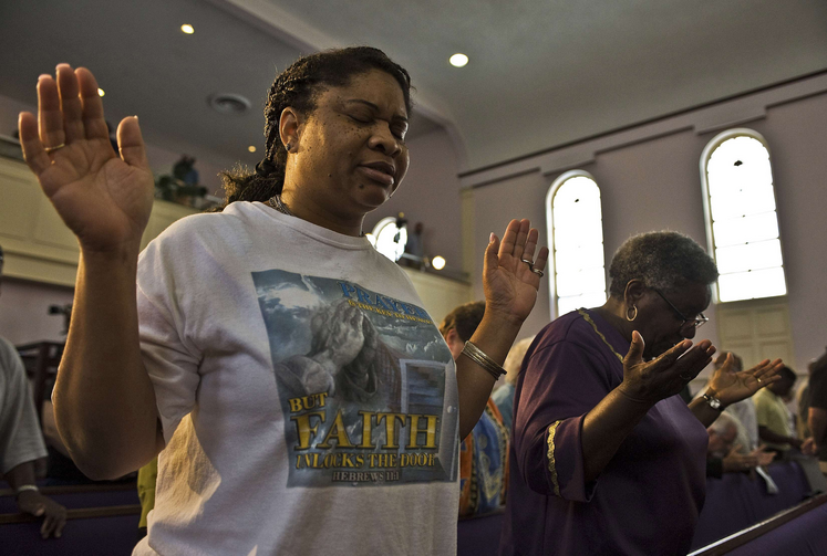 Women pray during service after George Zimmerman murder trial in Florida, July 13.