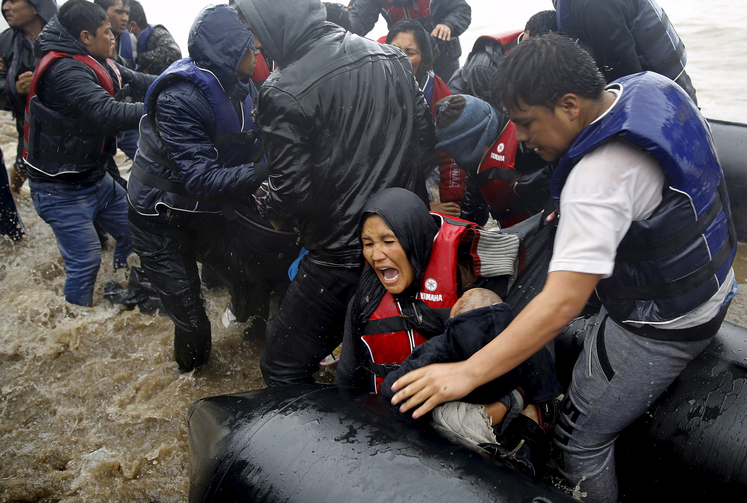 Afghan mother holds her baby as she struggles to disembark raft during a rainstorm in Lesbos, Greece, Oct. 23 (CNS photo/Yannis Behrakis, Reuters).