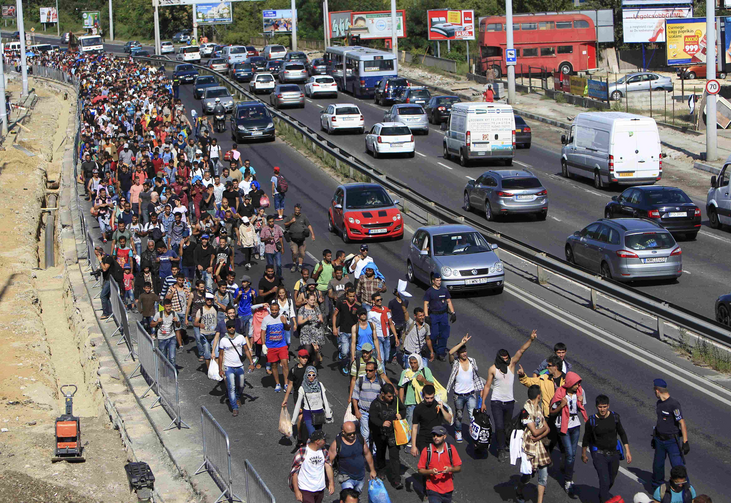 Migrants walk along a highway in Bicske, Hungary, near the border with Austria Sept. 4. (CNS/Bernadett Szabo, Reuters)