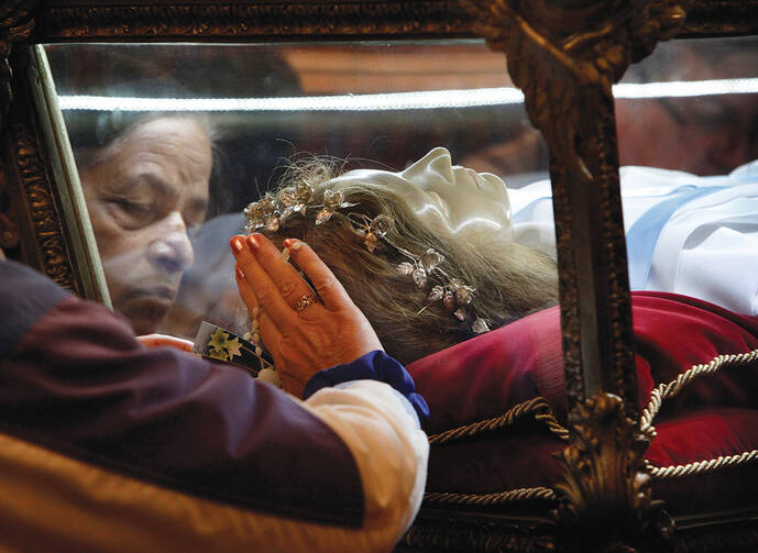 MYSTICAL ENCOUNTER. Worshippers venerate the relics of St. Maria Goretti at St. John Cantius Church in Chicago.