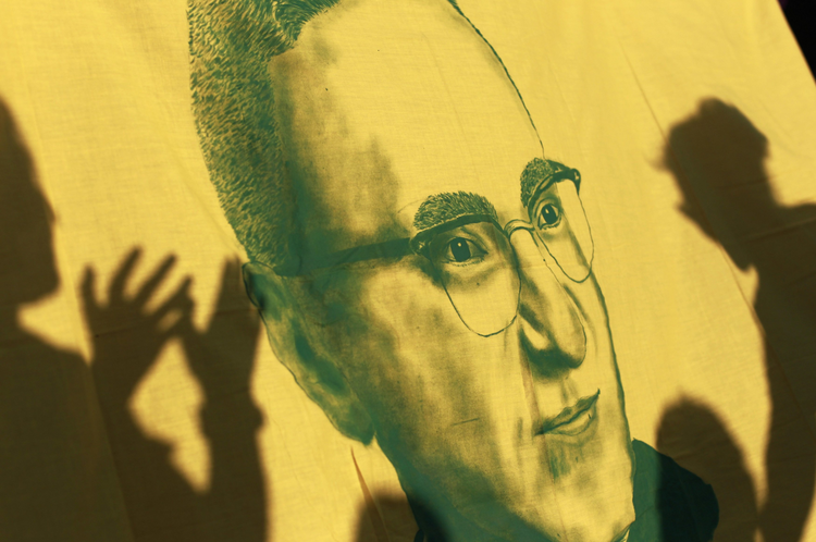 Flag with image of late Archbishop Oscar Romero seen during march prior to assassination anniversary in San Salvador