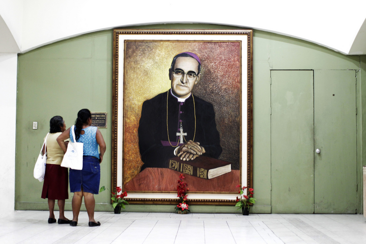 Salvadoran women look at a painting of slain Salvadoran Archbishop Oscar Romero at a cathedral in San Salvador.
