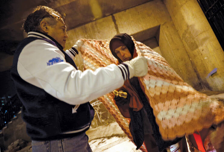 Dr. Patrick Angelo wraps a homeless man in blankets under the overpasses on Lower Wacker Drive in Chicago, ill.