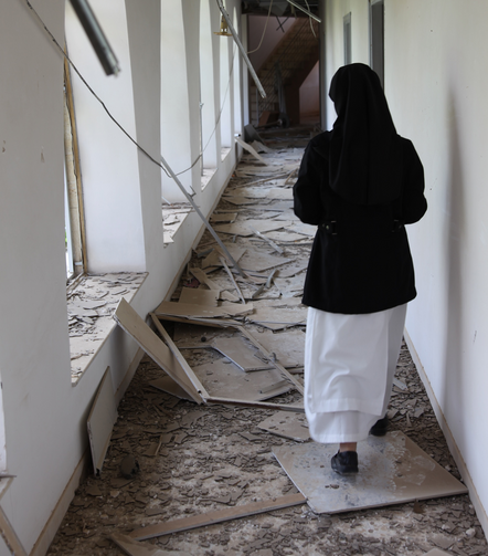 A nun walks through the hallway of the badly damaged convent of the Dominican Sisters of St. Catherine of Siena in Qaraqosh, Iraq. (CNS photo/courtesy John E. Kozar, CNEWA)