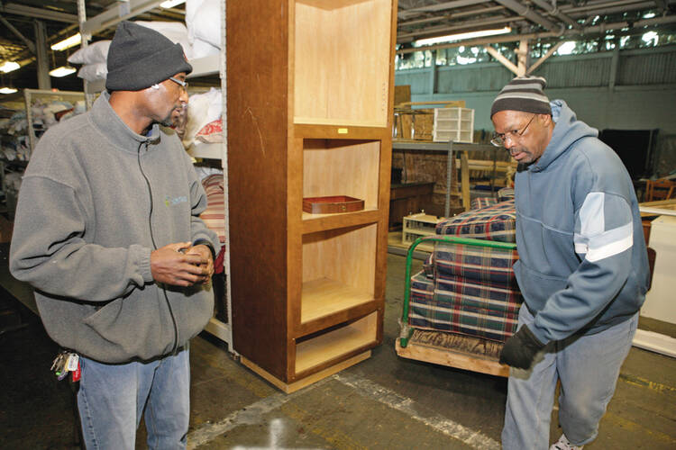 SUCCESS STORY. Michael Gordon, left, has become a manager for a furniture bank run by Caritas, an agency providing services to homeless people in Richmond, Va.