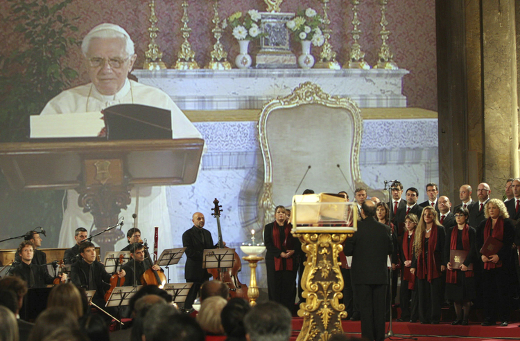 Pope Benedict XVI is shown reading the Bible in a live television feed projected inside the Basilica of the Holy Cross in Rome Oct. 5, 2008 (CNS photo/Alessandro De Meo, Reuters).