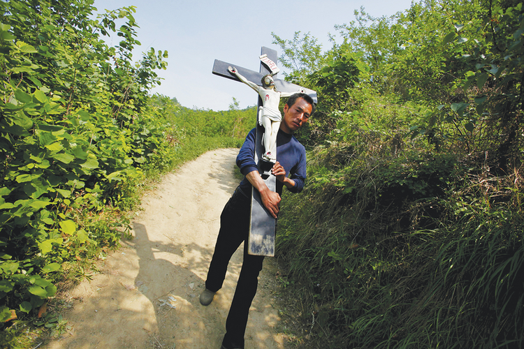 CROSS TO BEAR: A Chinese Catholic carries a crucifix during a pilgrimage in the Shanxi province of China in 2013.