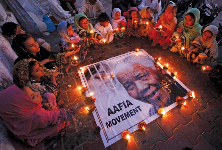 The world remembering Mandela: Children hold candles in a tribute to the former South African president in Karachi, Pakistan, on Dec. 6.