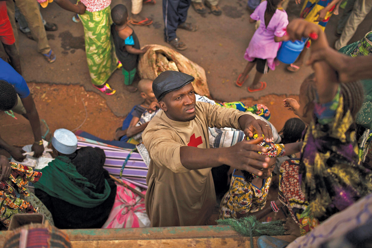 LIFE SAVER. Father Bernard Kenvi helps a Muslim child fleeing violence climb down from a truck in Bossemptele, in Central African Republic, on March 8.