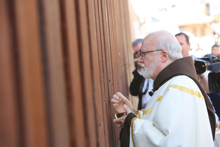 COMMUNION. Boston's Cardinal Seán O'malley at the border fence in Nogales, Ariz.