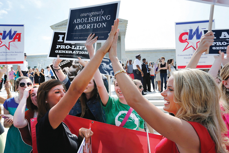 HIGH FIVE TO FOUR. Pro-life demonstrators on June 30 outside the U.S. Supreme Court in Washington.