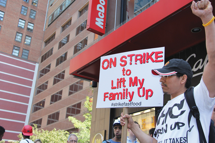 FAST FOOD, LOW WAGES. A worker joins a nation-wide campaign outside a Midtown Manhattan McDonald's