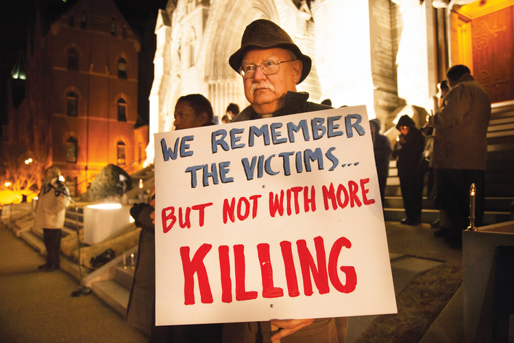 LETHAL DECISION. Deacon John Flanigan protests outside St. Louis University College Church on Jan. 28.