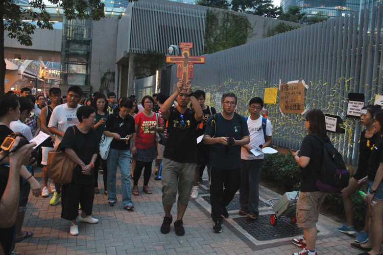Does Democracy Have a Prayer? Catholic youth join demonstrators outside a government office in Hong Kong on Sept. 30.